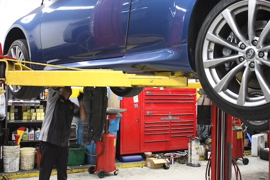 A mechanic working underneath a car at A+ Japanese Auto Repair in San Carlos, CA