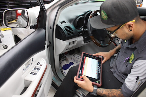 A mechanic checking a car's diagnostics at A+ Japanese Auto Repair in San Carlos, CA