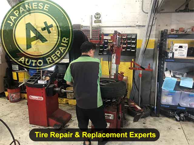 Tire Repair & Replacement Experts - Image shows a technician working on a tire - A+ Japanese Auto Repair Inc. - San Carlos, CA