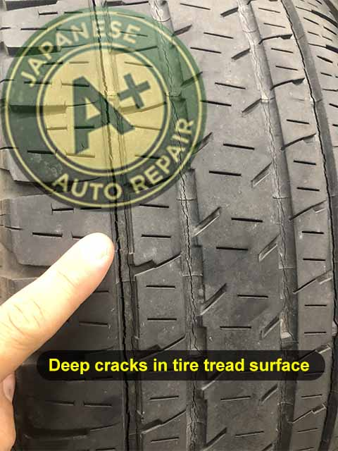 Image shows auto repair mechanic pointing to deep cracks in tire tread surface - A+ Japanese Auto Repair Inc. - San Carlos, CA